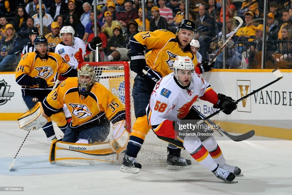 Ben Hanowski #58 of the Calgary Flames skates against Nick Spaling #13 of the Nashville Predators in front of Preators goalie Pekka Rinne #35 at the Bridgestone Arena on April 23, 2013 in Nashville, Tennessee.