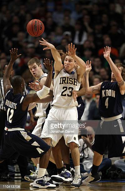 Ben Hansbrough of the Notre Dame Fighting Irish passes against Darryl Roberts and Steve McNees of the Akron Zips in the first half during the second...