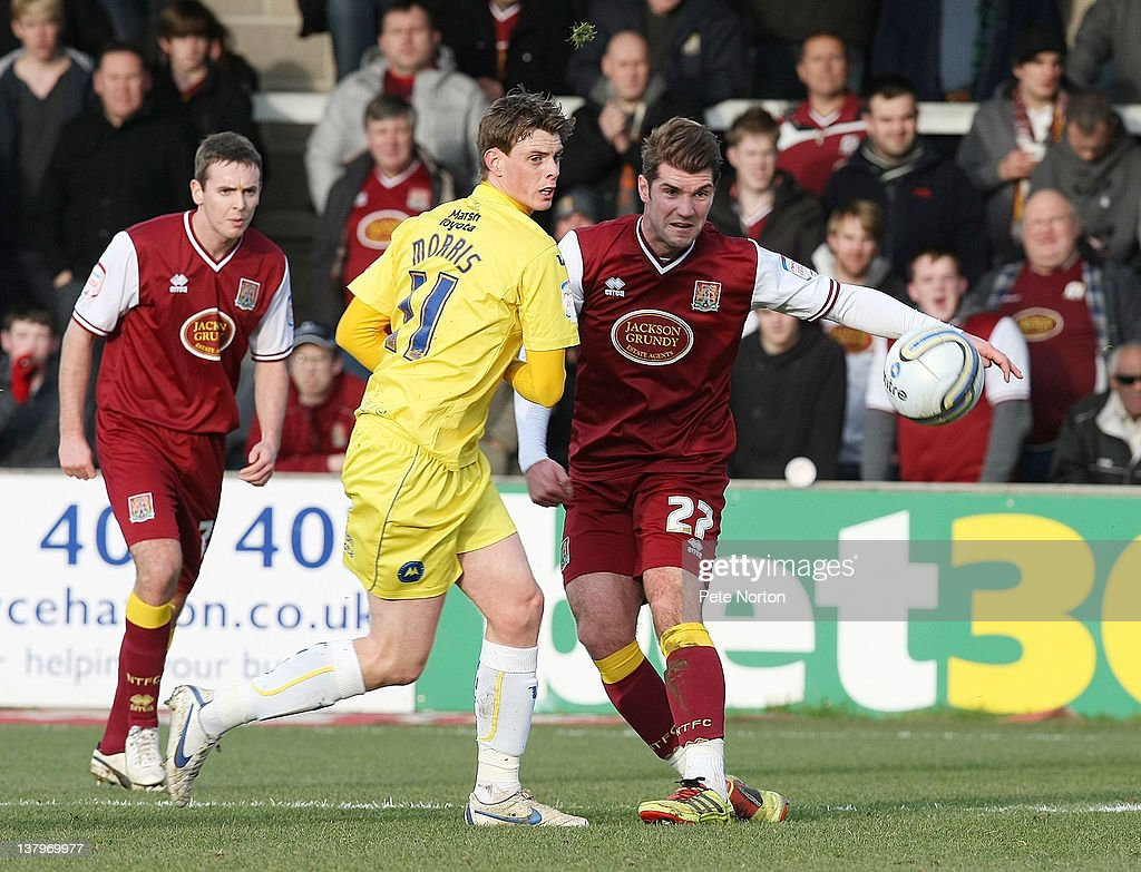 Ben Harding (R) of Northampton Town plays the ball watched by Ian Morris of Torquay United during the npower League Two match between Torquay United and Northampton Town at Plainmoor on January 28, 2012 in Torquay, England.