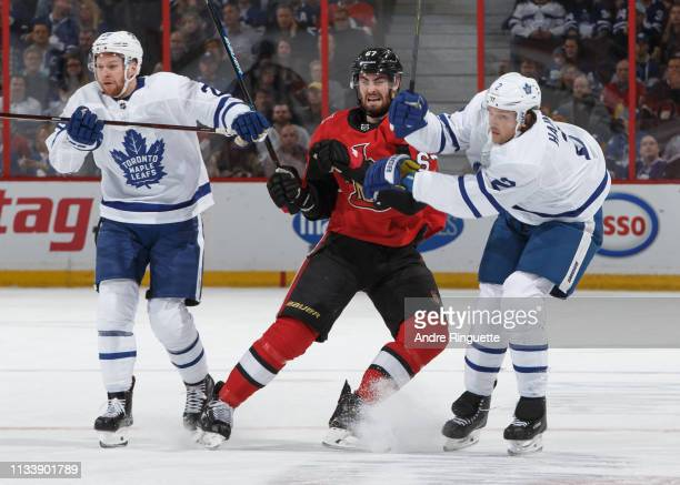 Ben Harpur of the Ottawa Senators battles for position against Connor Brown and Ron Hainsey of the Toronto Maple Leafs at Canadian Tire Centre on...
