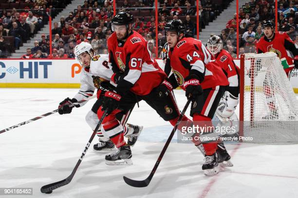 Ben Harpur of the Ottawa Senators clears the puck as teammates JeanGabriel Pageau and Mike Condon defend the net against Nick Schmaltz of the Chicago...