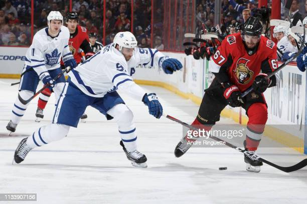 Ben Harpur of the Ottawa Senators controls the puck against John Tavares of the Toronto Maple Leafs at Canadian Tire Centre on March 30 2019 in...