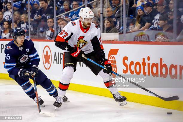 Ben Harpur of the Ottawa Senators plays the puck along the boards as Mark Scheifele of the Winnipeg Jets gives chase during first period action at...