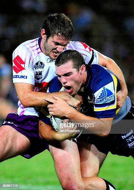 Ben Harris of the Cowboys is tackled by Dallas Johnson of the Storm during the round seven NRL match between the North Queensland Cowboys and the...