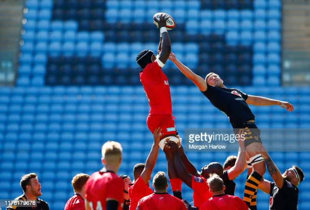 Ben Harris of Wasps jumps for a line out with Joel Kpoko of Saracens during the Premiership Rugby Cup match between Wasps and Saracens at The Ricoh...