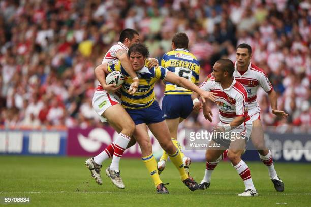 Ben Harrison of Warrington is tackled during the semifinal match of the Carnegie Challenge Cup between Wigan Warriors and Warrington Wolves at the...