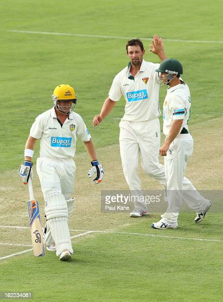 Ben Hilfenhaus of the Tigers celebrates with Jon Wells after dismissing Marcus Harris of the Warriors during day one of Sheffield Shield match...