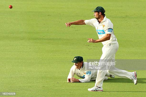 Ben Hilfenhaus of the Tigers fields the ball as George Bailey looks on during day one of Sheffield Shield match between the Western Australia...