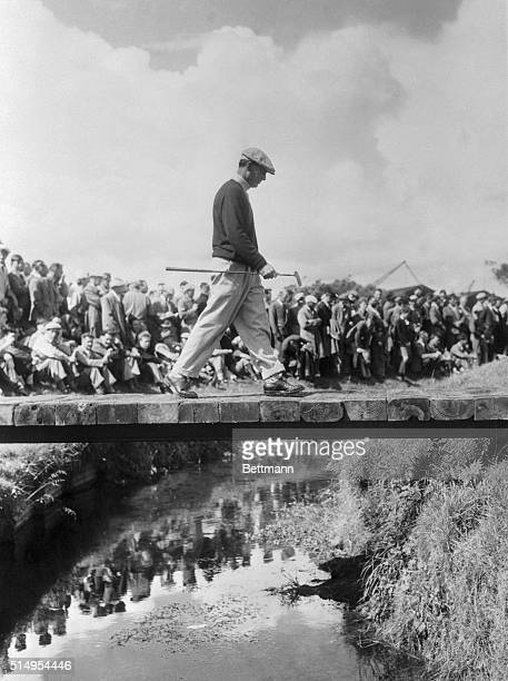 Ben Hogan crosses a stream on the Carnoustie Golf Course while a huge crowd awaits his next shot in the British Open Championship The American champ...