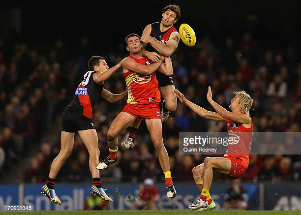 Ben Howlett of the Bombers attempts to mark over the top of Thomas Murphy of the Suns during the round 12 AFL match between the Essendon Bombers and...