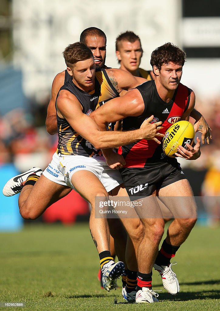 Ben Howlett of the Bombers is tackled by Ricky Petterd of the Tigers during the round two AFL NAB Cup match between the Essendon Bombers and the Richmond Tigers at Wangaratta Showgrounds on March 2, 2013 in Wangaratta, Australia.