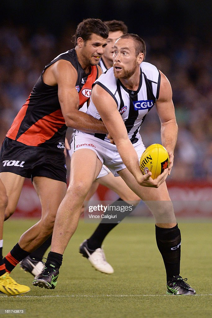 Ben Hudson of the magpies looks to handball away from Patrick Ryder of the bombers during the round one AFL NAB Cup match between the Collingwood Magpies and the Essendon Bombers at Etihad Stadium on February 15, 2013 in Melbourne, Australia.