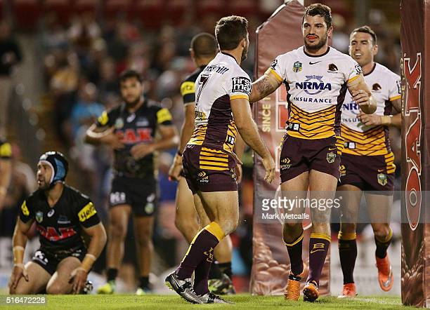 Ben Hunt of the Broncos celebrates scoring a try with team mates Matthew Gillett and Darius Boyd during the round three NRL match between the Penrith...