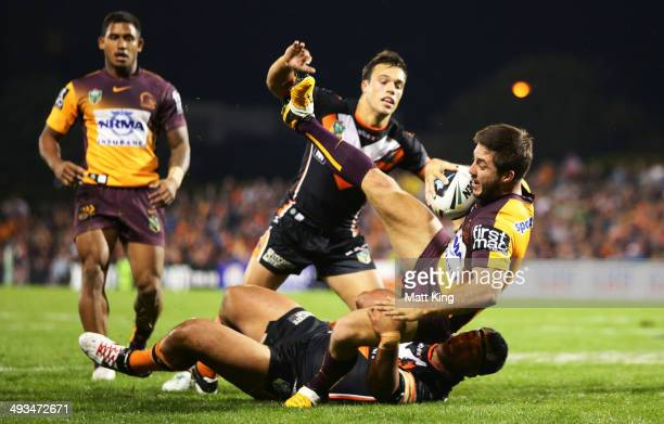 Ben Hunt of the Broncos is tackled during the round 11 NRL match between the Wests Tigers and the Brisbane Broncos at Campbelltown Sports Stadium on...