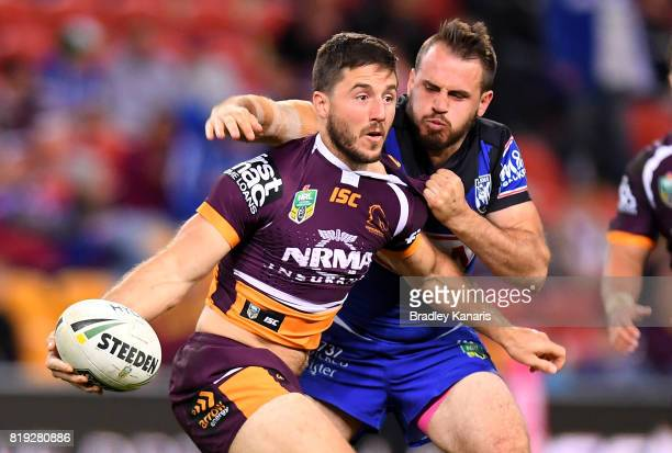 Ben Hunt of the Broncos offloads as he is pressured by the defence of Josh Reynolds of the Bulldogs during the round 20 NRL match between the...