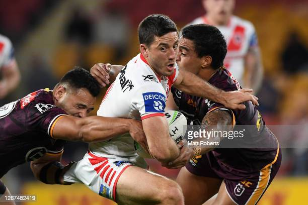 Ben Hunt of the Dragons is tackled during the round 15 NRL match between the Brisbane Broncos and the St George Illawarra Dragons at Suncorp Stadium...