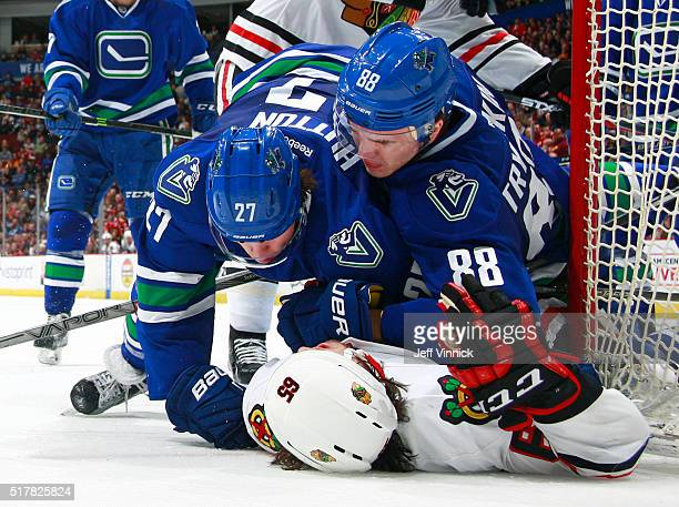 Ben Hutton and Nikita Tryamkin of the Vancouver Canucks pin Andrew Shaw of the Chicago Blackhawks during their NHL game at Rogers Arena March 27 2016...