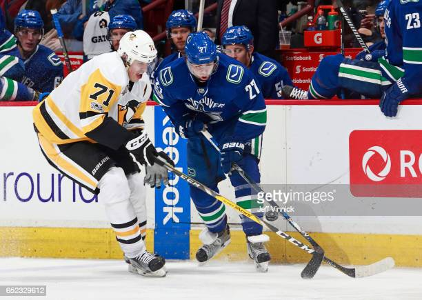 Ben Hutton of the Vancouver Canucks and Evgeni Malkin of the Pittsburgh Penguins battle for a loose puck during their NHL game at Rogers Arena March...