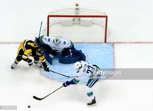 Ben Hutton of the Vancouver Canucks clears a puck away from the front of Anders Nilsson as Tom Kuhnhackl of the Pittsburgh Penguins attempts a screen...