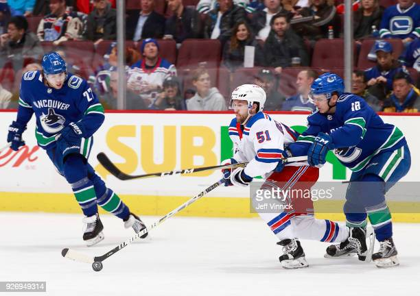 Ben Hutton of the Vancouver Canucks looks on as teammate Jake Virtanen checks David Desharnais of the New York Rangers during their NHL game at...