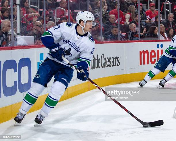 Ben Hutton of the Vancouver Canucks skates around the net with the puck against the Detroit Red Wings during an NHL game at Little Caesars Arena on...
