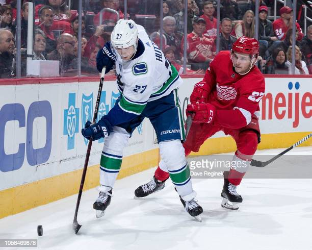 Ben Hutton of the Vancouver Canucks skates with the puck behind the net followed by Michael Rasmussen of the Detroit Red Wings during an NHL game at...