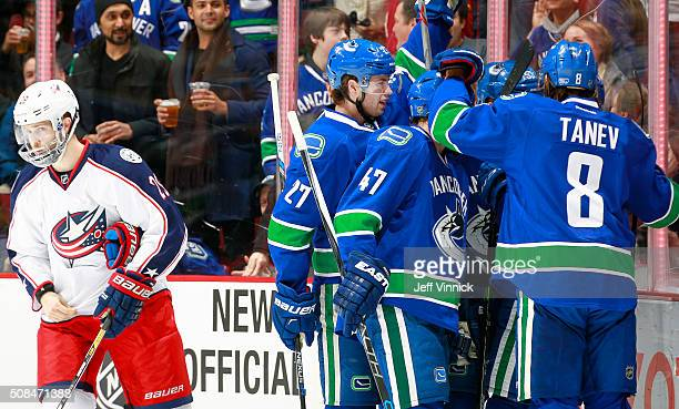 Ben Hutton, Sven Baertschi and Christopher Tanev of the Vancouver Canucks congratulate goal scorer Linden Vey of the Vancouver Canucks while Cody...