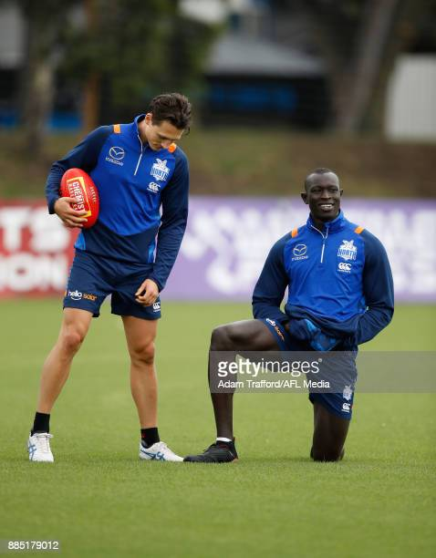 Ben Jacobs and Majak Daw of the Kangaroos watch on as played prepare for the yoyo test during the North Melbourne Kangaroos training session at Arden...