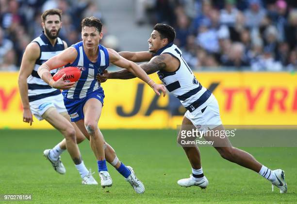 Ben Jacobs of the Kangaroos is tackled by Tim Kelly of the Cats during the round 12 AFL match between the Geelong Cats and the North Melbourne...