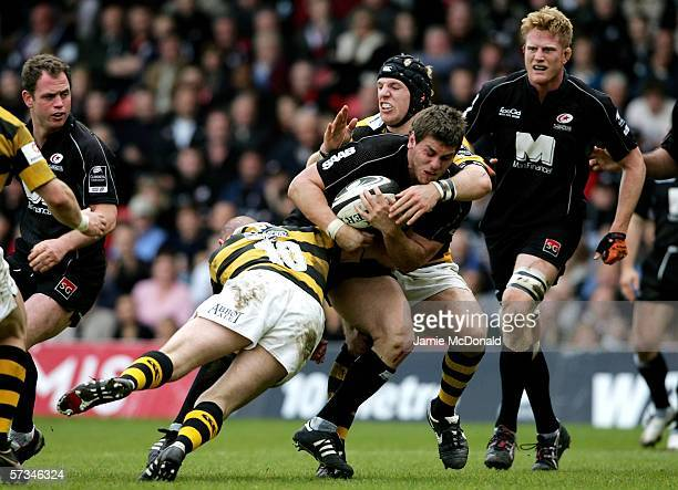 Ben Johnson of Saracens is tackled by Alex King and Richard Birkett of Wasps during the Guinness Premiership match between Saracens and London Wasps...