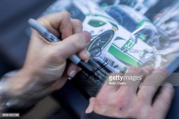 Ben Keating signs an autograph card before qualifying for the Motul Petit Le Mans at Road Atlanta on October 6, 2017 in Braselton, Georgia.