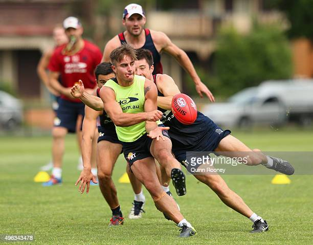 Ben Kennedy of the Demons handballs whilst being tackled by Alex NealBullen during a Melbourne Demons AFL preseason training session at Gosch's...