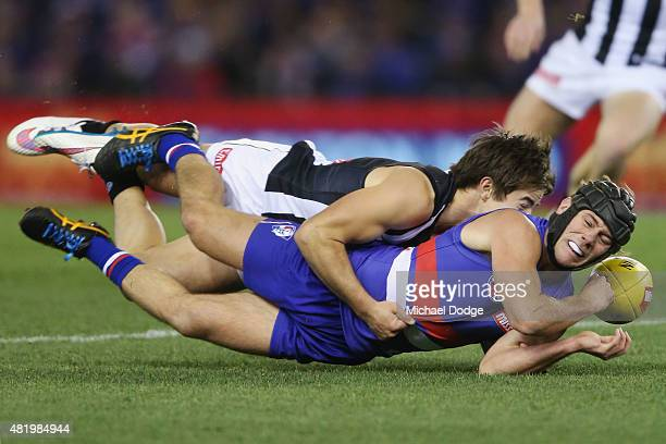 Ben Kennedy of the Magpies tackles Caleb Daniel of the Bulldogs during the round 17 AFL match between the Western Bulldogs and the Collingwood...