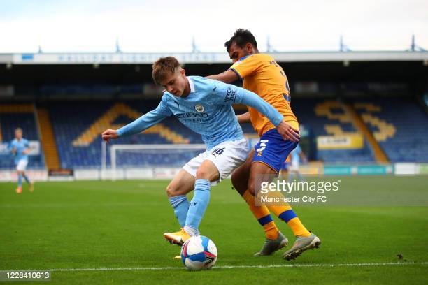 Ben Knight of Manchester City in action with Malvind Benning of Mansfield Town during the EFL Trophy match between Mansfield Town and Manchester City...