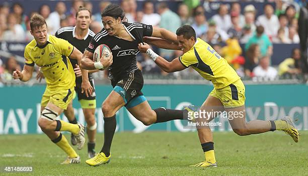Ben Lam of New Zealand is tackled during the Cup semifinal match between Australia and New Zealand during day three of the 2014 Hong Kong Sevens at...