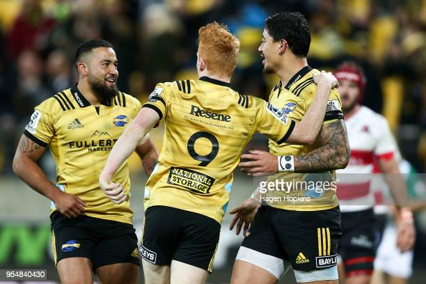 Ben Lam of the Hurricanes celebrates his try with teammates Finlay Christie and Matt Proctor during the round 12 Super Rugby match between the...