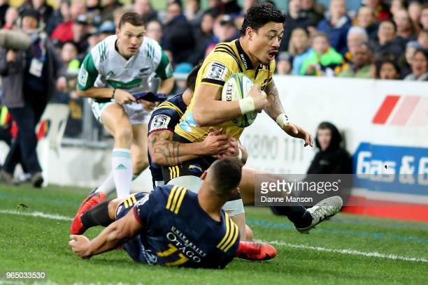 Ben Lam of the Hurricanes is tackled by Rob Thompson of the Highlanders during the round 16 Super Rugby match between the Highlanders and the...