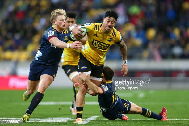 Ben Lam of the Hurricanes is tackled by Scott Gregory and Mitch Hunt of the Highlanders during the round 5 Super Rugby Aotearoa match between the...