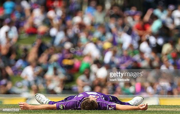 Ben Laughlin of the Hurricanes lays on the ground after falling whilst fielding off his own bowling during the Big Bash League match between the...