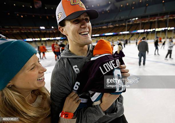 Ben Lovejoy holds his son with his wife during the family skate after the team practice for the 2014 Coors Light NHL Stadium Series against the Los...