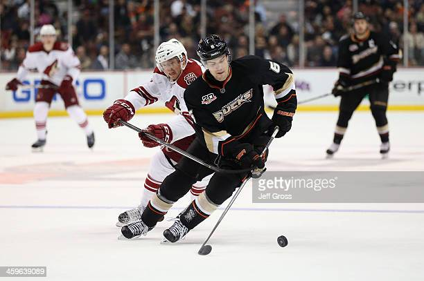 Ben Lovejoy of the Anaheim Ducks is pursued by Rob Klinkhammer of the Phoenix Coyotes for the puck in the second period at Honda Center on December...