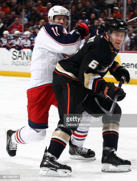 Ben Lovejoy of the Anaheim Ducks skates against Matt Calvert of the Columbus Blue Jackets on February 3 2014 at Honda Center in Anaheim California