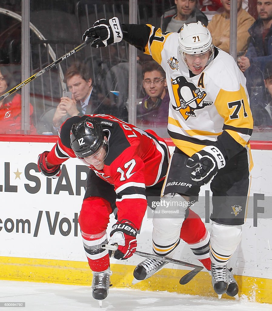 Ben Lovejoy #12 of the New Jersey Devils and Evgeni Malkin #71 of the Pittsburgh Penguins battle for the puck in the third period of an NHL hockey game at Prudential Center on December 27, 2016 in Newark, New Jersey. Penguins won 5-2.