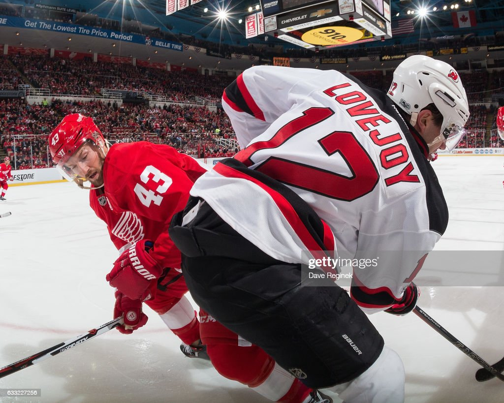 Ben Lovejoy #12 of the New Jersey Devils battles along the boards with Darren Helm #43 of the Detroit Red Wings during an NHL game at Joe Louis Arena on January 31, 2017 in Detroit, Michigan.