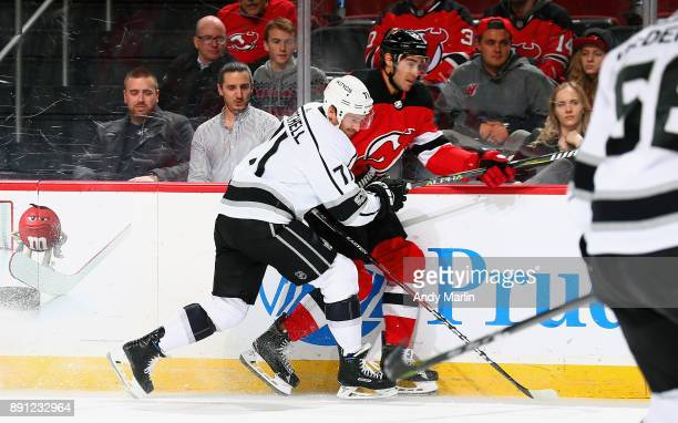 Ben Lovejoy of the New Jersey Devils is checked at the boards by Torrey Mitchell of the Los Angeles Kings during the game at Prudential Center on...
