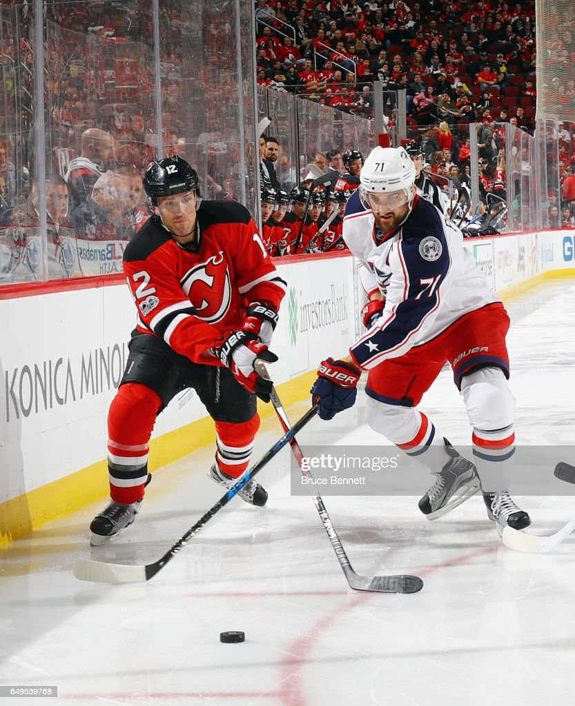 Ben Lovejoy #12 of the New Jersey Devils skates against Nick Foligno #71 of the Columbus Blue Jackets at the Prudential Center on March 5, 2017 in Newark, New Jersey.