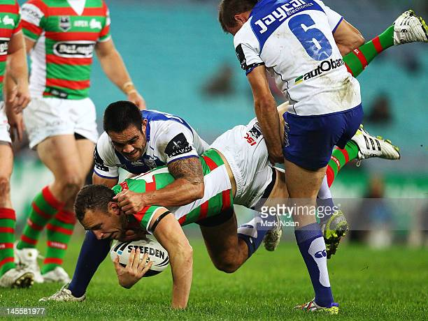 Ben Lowe of the Rabbitohs is tackled during the round 13 NRL match between the Canterbury Bulldogs and the South Sydney Rabbitohs at ANZ Stadium on...