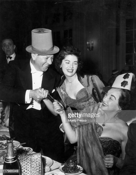 Ben Lyon pulling a cracker with his wife Bebe Daniels with their daughter Barbara Lyon at the New Year's Eve Limelight Ball at the Savoy hotel in...