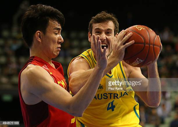 Ben Madgen of Australia drives to the basket against Fei Cao of China during the 2014 Sino-Australia Challenge match between the Australian Boomers...