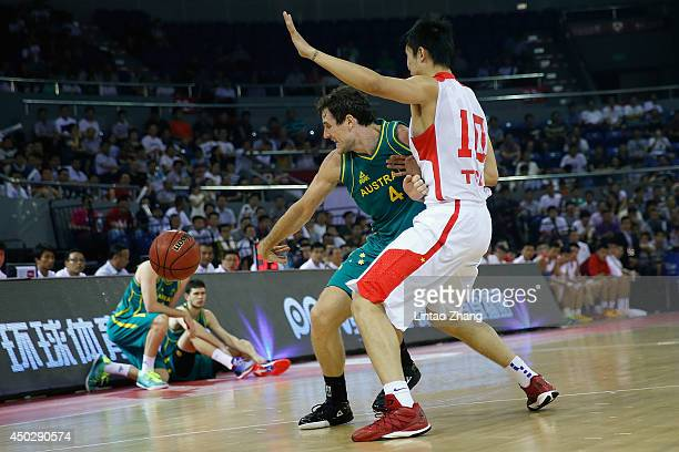 Ben Madgen of Australia looks to pass against Ding Yanyuhang of China during the 2014 SinoAustralia Men's International Basketball Challenge match...